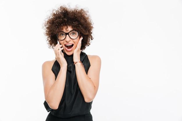 Empresaria feliz emocionada en anteojos hablando por teléfono móvil Foto gratis