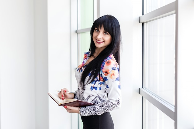 Empresaria hermosa joven que se coloca cerca de la ventana, escribiendo en un cuaderno, mirando la sonrisa de la cámara. Foto Premium