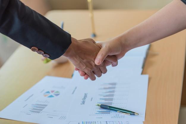 La empresaria y el hombre de negocios que sacuden entregan el escritorio con los papeles en la oficina. Foto Premium