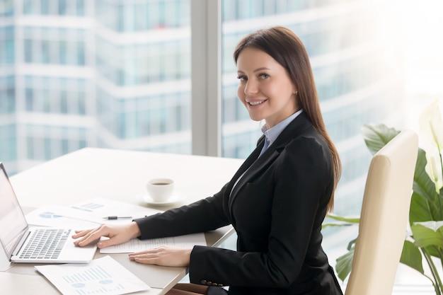 Empresaria joven alegre sonriente que trabaja en el escritorio de oficina con el ordenador portátil Foto gratis