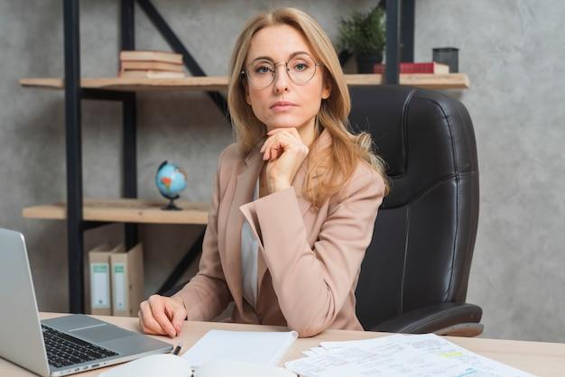Empresaria joven confiada que se sienta en el lugar de trabajo con el ordenador portátil en la oficina Foto gratis