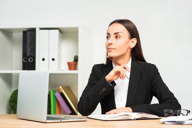 Empresaria joven contemplada que se sienta en el escritorio de oficina con el ordenador portátil en el escritorio Foto gratis