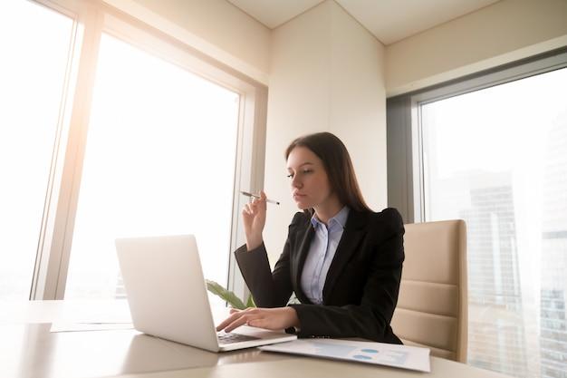 Empresaria joven en cuestión seria que trabaja en el escritorio de oficina usando la computadora portátil Foto gratis