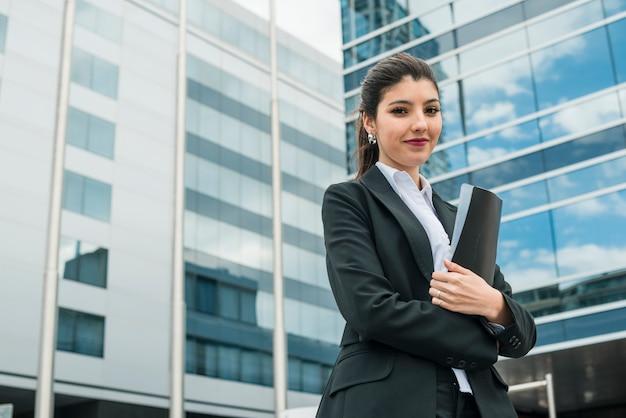 Empresaria joven feliz que sostiene la carpeta en la mano que se coloca delante del edificio Foto gratis