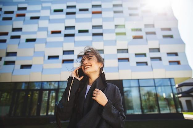 Empresaria joven que habla en el teléfono móvil durante descanso para tomar café al aire libre, cerca del edificio de oficinas. Foto Premium