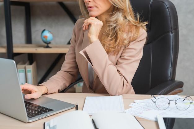 Empresaria joven que usa el ordenador portátil con el diario y documentos en el lugar de trabajo Foto gratis