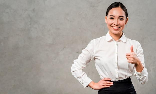 Empresaria joven sonriente confiada que muestra el pulgar encima de la muestra que se opone a la pared gris Foto gratis