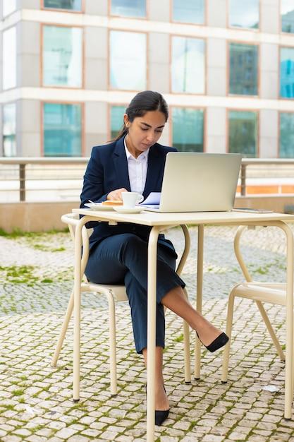 Empresaria con laptop y papeles en café Foto gratis