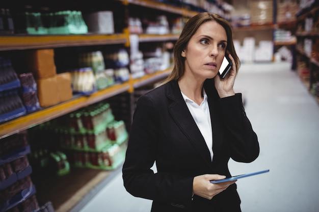 Empresaria en una llamada telefónica en el almacén Foto Premium