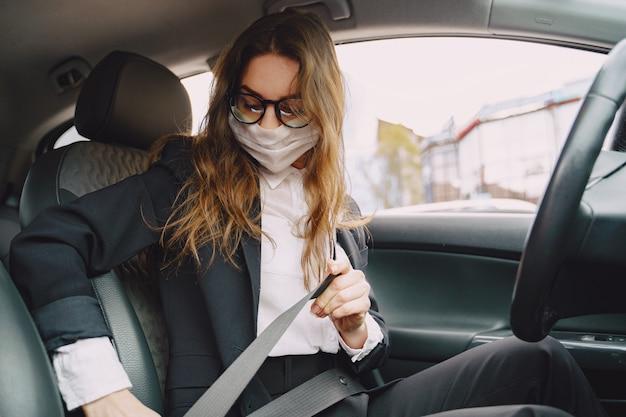 Empresaria en una máscara negra sentada dentro de un automóvil Foto gratis