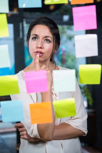 Empresaria mirando nota adhesiva Foto Premium
