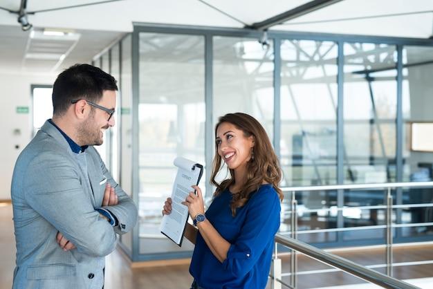 La empresaria mostrando documentos al director de marketing en la oficina de la empresa Foto gratis