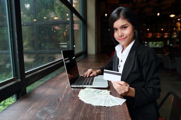 Empresaria mostrando tarjeta de crédito con computadora y billetes en el escritorio de madera Foto Premium