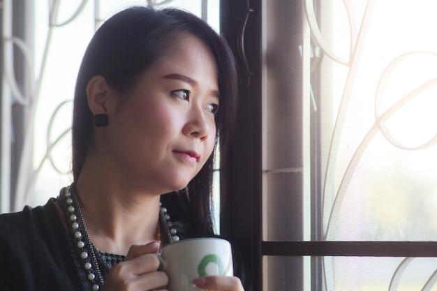 Empresaria de pie y pensando en la ventana y tomando café. Foto Premium