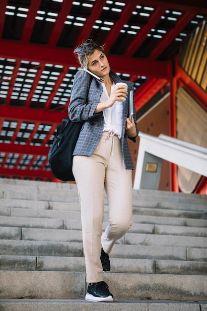 Empresaria que habla en el teléfono móvil que sostiene la taza de café para llevar y la tableta digital Foto gratis