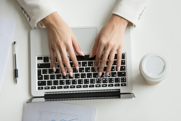 Empresaria que trabaja en la computadora portátil, manos escribiendo en el teclado, vista desde arriba Foto gratis