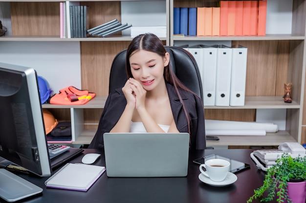Empresaria que trabaja en la oficina con una sonrisa mientras está sentado. Foto gratis