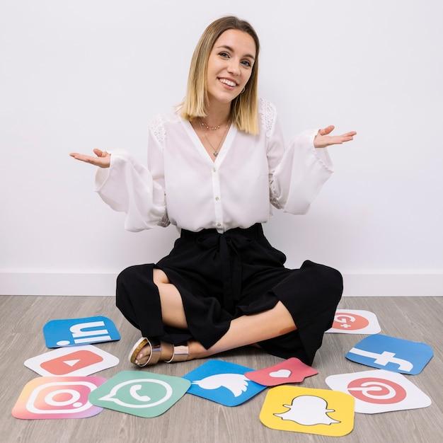 Empresaria sentado en el piso con iconos de redes sociales encogiéndose de hombros Foto gratis