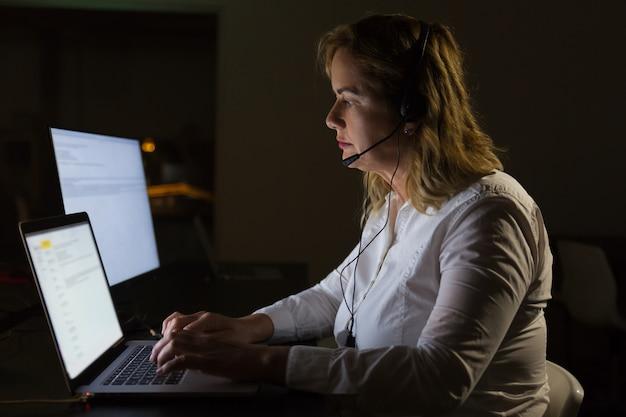 Empresaria seria en auriculares escribiendo en la computadora portátil Foto gratis