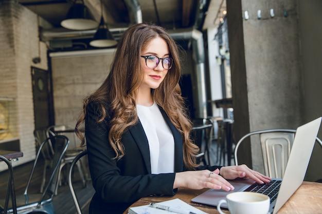 Empresaria sonriente escribiendo en un portátil sentado en un café Foto gratis