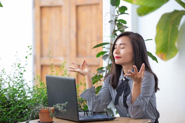 La empresaria sonriente muestra gestos para meditar Foto gratis