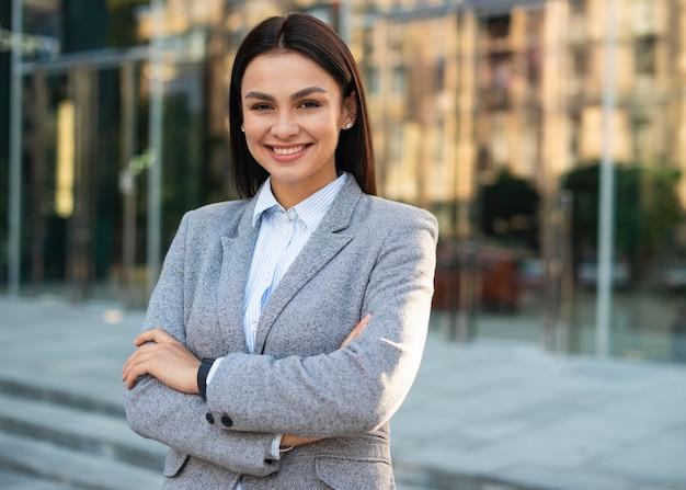 Empresaria sonriente posando al aire libre con los brazos cruzados y copie el espacio Foto gratis