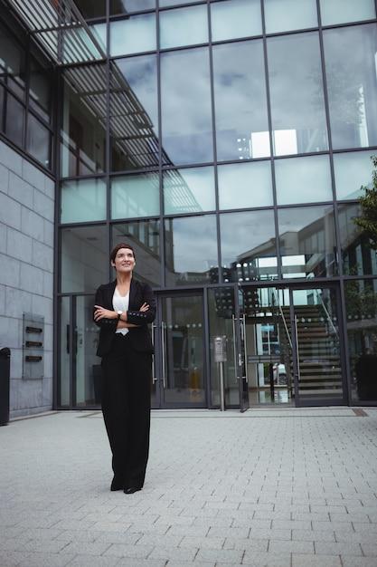 Empresaria sonriente que se coloca en premisas de oficina Foto Premium