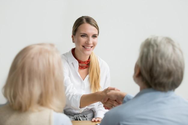 Empresaria sonriente que sacude la mano de senior hr en entrevista de trabajo Foto gratis