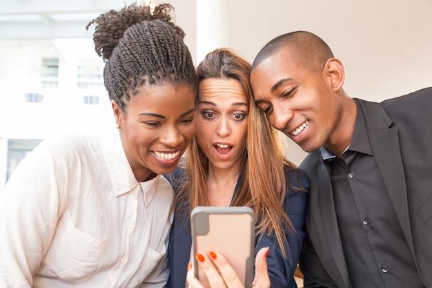 Empresaria sorprendida y colegas sonrientes tomando selfie Foto gratis