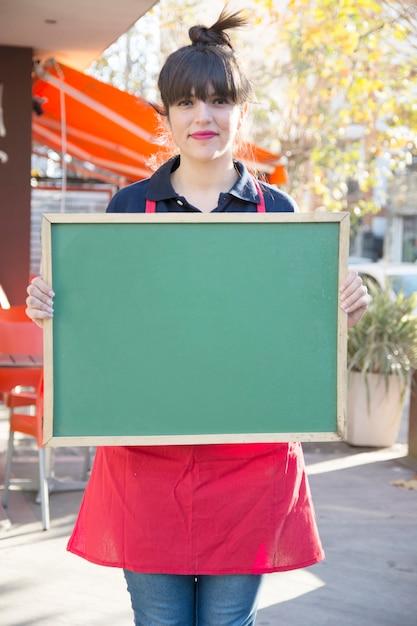 Empresaria sosteniendo el tablero de menú verde en blanco en el café al aire libre Foto gratis