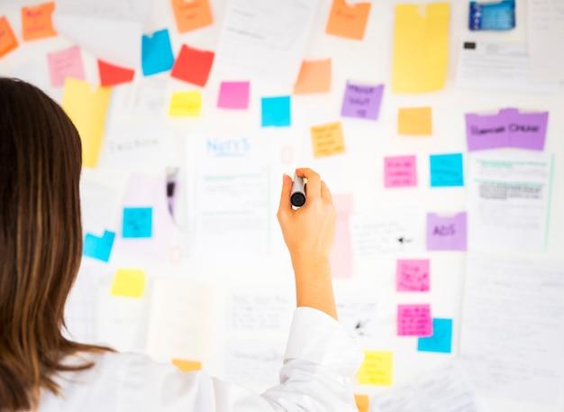 Empresaria trabajando con notas en una oficina Foto gratis