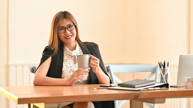 Empresaria ubicando y sosteniendo una taza de café Foto Premium