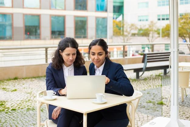 Empresarias con laptop en café al aire libre Foto gratis