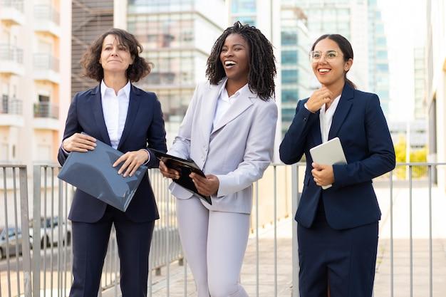 Empresarias con papeles y dispositivo digital. colegas femeninas multiétnicas que sostienen la pc y los papeles de la tableta al aire libre. concepto de negocio Foto gratis