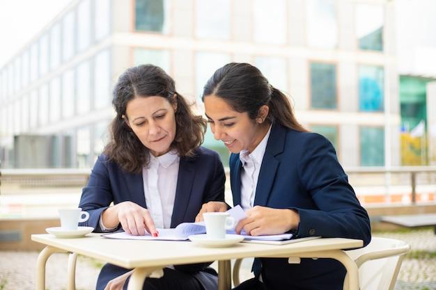 Empresarias que trabajan con documentos en café al aire libre Foto gratis