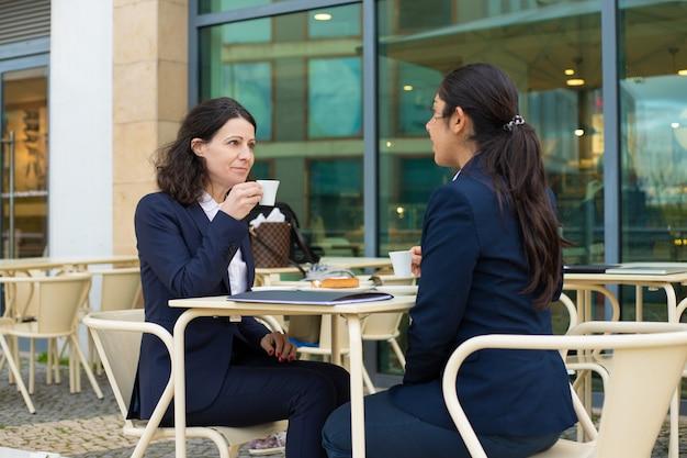 Empresarias tomando café en la cafetería al aire libre Foto gratis