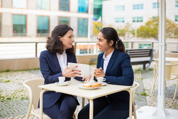 Empresarias tomando café y usando tablet pc Foto gratis