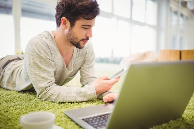 Empresario acostado en la alfombra mientras usa la computadora portátil y el teléfono móvil Foto Premium