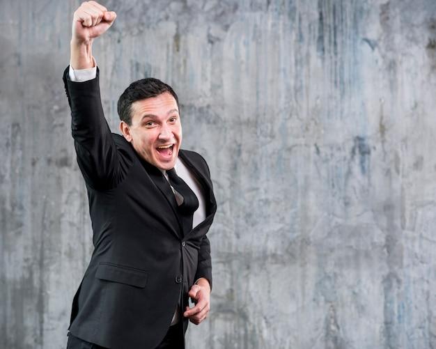 Empresario adulto levantando el puño y sonriendo Foto gratis