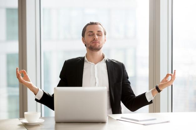 Empresario alivia el estrés laboral con la meditación. Foto gratis