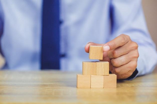 Empresario apilando bloques de madera en pasos. concepto de éxito del crecimiento empresarial Foto Premium