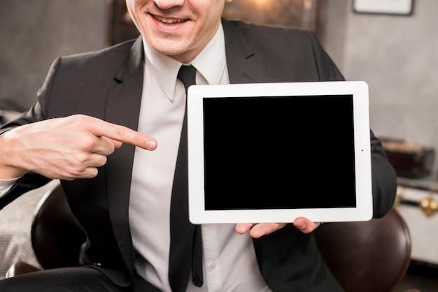 Empresario apuntando a la tableta con pantalla en blanco Foto gratis