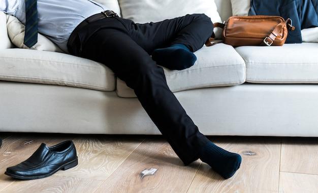 Empresario asiático tomando descanso tendido en el sofá Foto gratis
