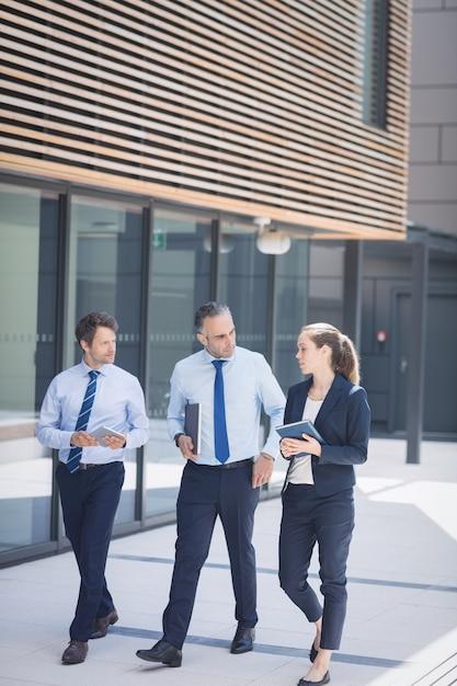 Empresario caminando con colegas fuera del edificio de oficinas Foto gratis