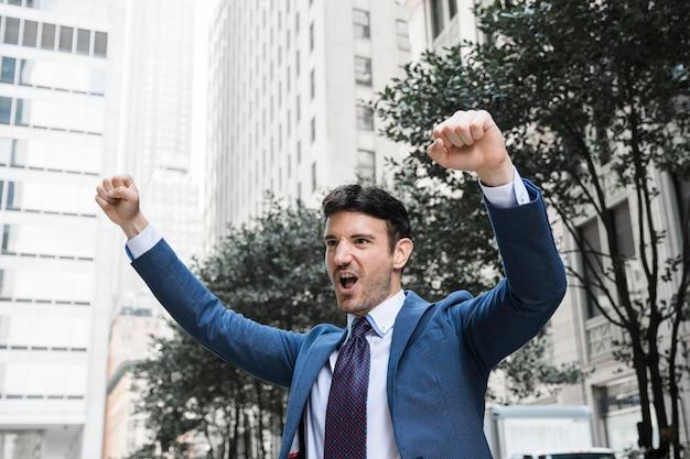 Empresario celebrando el éxito en la calle Foto gratis