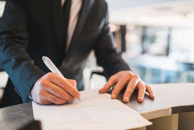 Empresario check-in en la recepción del hotel. Foto Premium