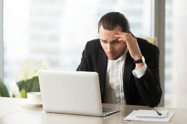 Empresario confundido molesto mirando la pantalla del portátil Foto gratis