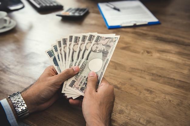 Empresario contando dinero yen japonés billetes Foto Premium