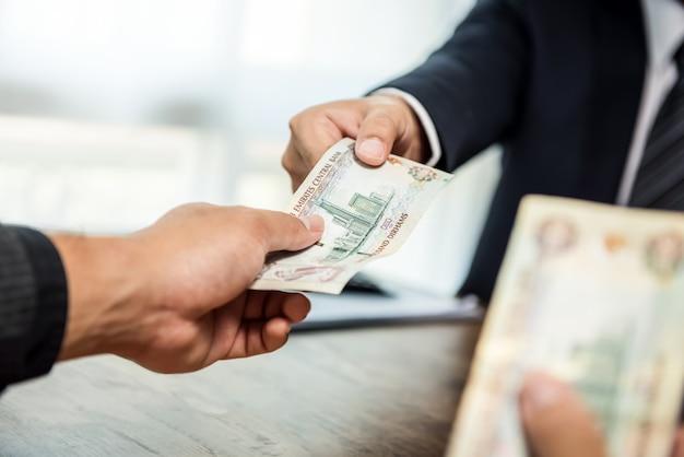 Empresario dando dinero dirham de emiratos árabes unidos Foto Premium