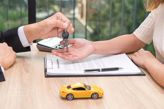 Empresario dando la llave del coche sobre el documento de solicitud de préstamo de coche Foto Premium